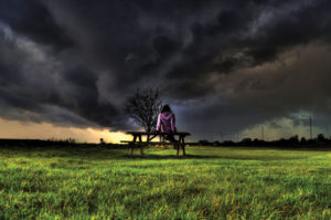 English weather idioms - girl on bench in front of storm